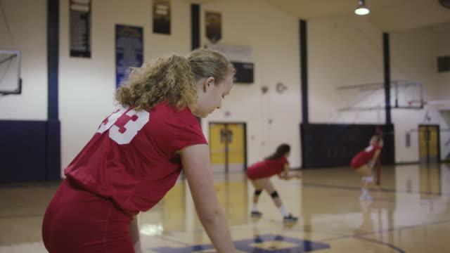 weibliche high-school-volleyball-spieler dienen einen volleyball während eines spiels - volleyball spielball stock-videos und b-roll-filmmaterial