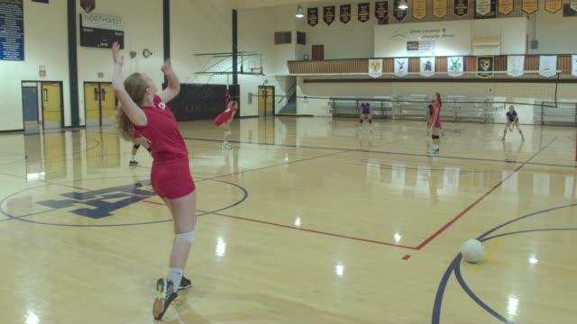 vídeos de stock, filmes e b-roll de jogadores de vôlei feminino ensino médio, competindo em um jogo - colégio educação