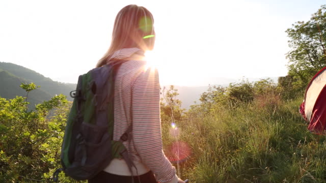 female hiker approaches tent, removes backpack, sunrise - 腰に手を当てる点の映像素材/bロール