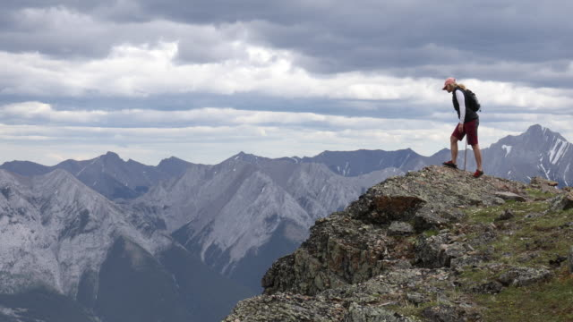 female hiker arrives on mountain summit, looks off to view - climbing equipment stock videos & royalty-free footage