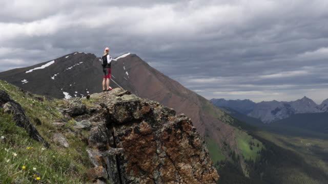 female hiker arrives on mountain summit, looks off to view - ジャスパー国立公園点の映像素材/bロール
