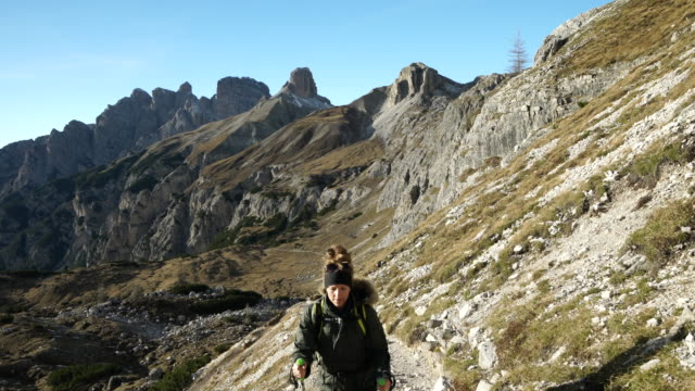 female hiker ascending mountain trail at sunset - kosmetisches stirnband stock-videos und b-roll-filmmaterial