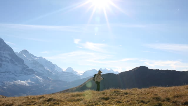 female hiker ascends grass meadow, snow capped mountains - kletterausrüstung stock-videos und b-roll-filmmaterial