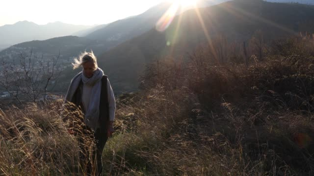 female hiker ascends grassy slope at sunrise - cardigan sweater stock videos & royalty-free footage