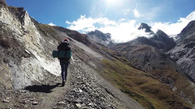 Vrouwelijke wandelaar bestijgt bergpad boven vallei