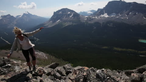 female hiker ascends mountain ridge to summit - one mid adult woman only stock videos & royalty-free footage