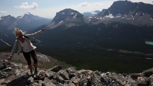 female hiker ascends mountain ridge to summit - human limb stock videos & royalty-free footage