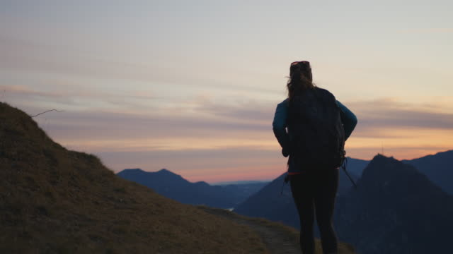 female hiker ascends mountain trail to view of city, lake and sunset below - leggings stock videos & royalty-free footage