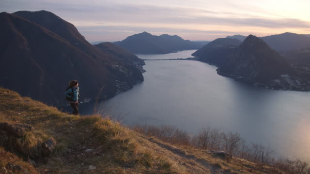 female hiker ascends mountain trail, view of lake and mountains below - rucksack stock-videos und b-roll-filmmaterial