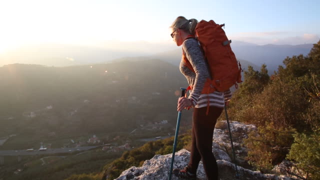 female hiker ascends onto rock ledge, hills distant, sunrise - one mature woman only stock videos & royalty-free footage
