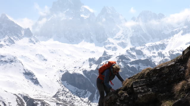 Female hiker ascends ridge above snow capped mountain