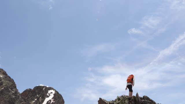 Female hiker ascends ridge crest in mountain landscape