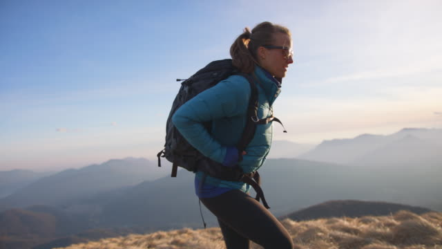 female hiker ascends ridge, view of lake and mountains below - rucksack stock videos & royalty-free footage