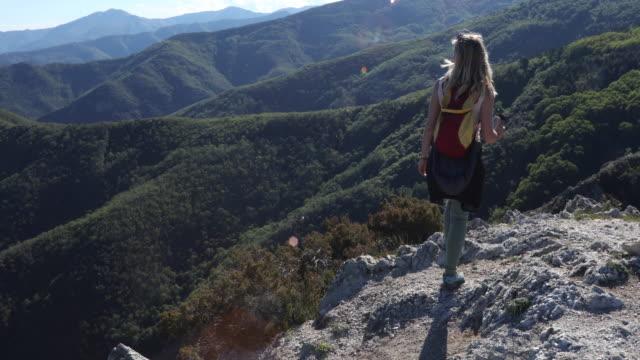 Weiblicher Wanderer steigt Felskamm über Berge, Meer
