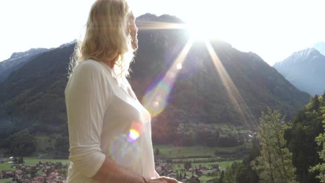 vídeos y material grabado en eventos de stock de female hiker ascends through alpine meadow, mountains distant - una sola mujer madura