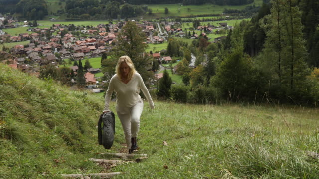 female hiker ascends through alpine meadow, mountains distant - dramatic landscape stock videos and b-roll footage