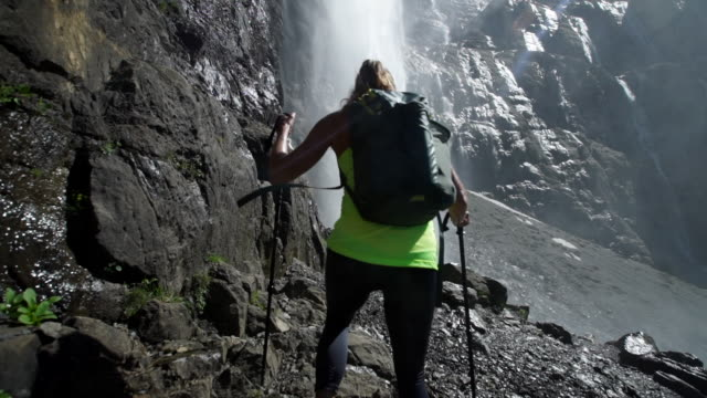 Female hiker ascends trail towards waterfall