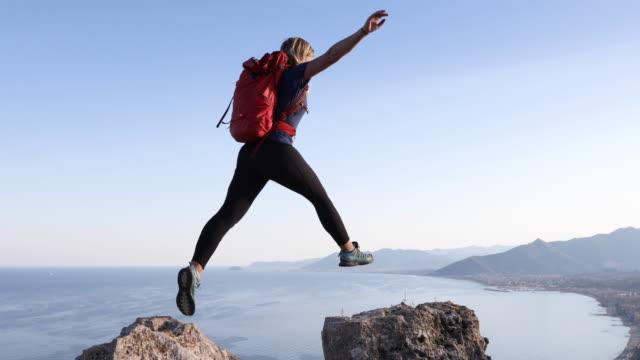 female hiker bounds between rock summits - danger stock videos & royalty-free footage