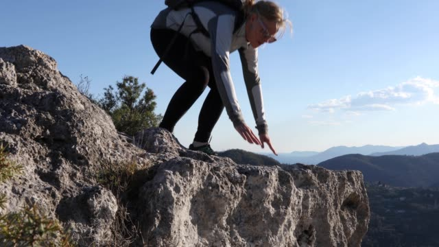 female hiker carefully walks to cliff edge, looks out - lying down stock videos & royalty-free footage