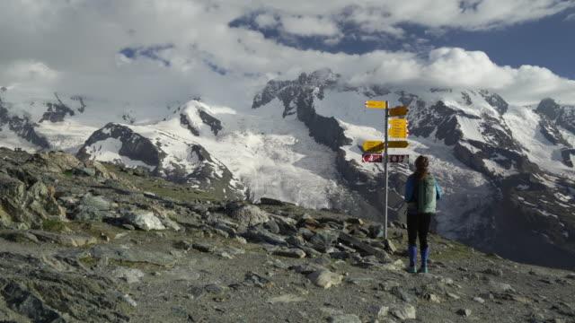 Kvinnliga hiker kontrollerar tecken för riktningar i Alperna