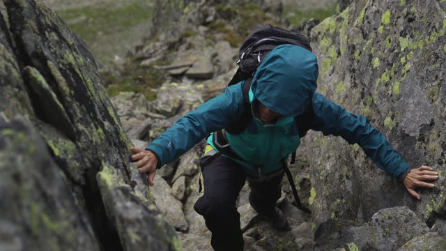 female hiker climbing up a rocky path on a mountain - risk bildbanksvideor och videomaterial från bakom kulisserna