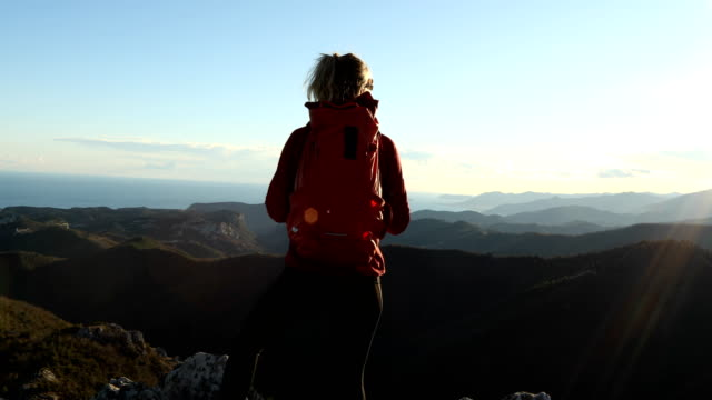 female hiker climbs above sea and mountains at sunrise - alpinismo video stock e b–roll
