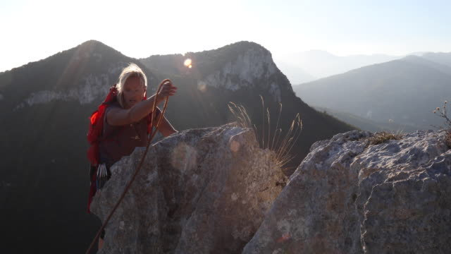 female hiker climbs along mountain summit at sunrise - one mature woman only stock videos & royalty-free footage