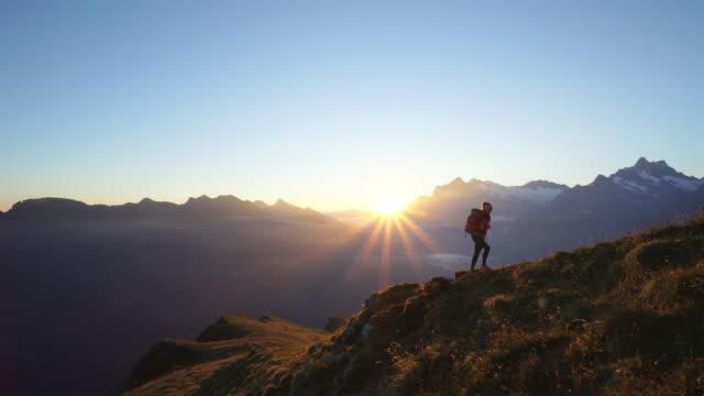 weibliche wanderer klettert schmalen grat bei sonnenaufgang in den schweizer bergen - der weg nach vorne stock-videos und b-roll-filmmaterial