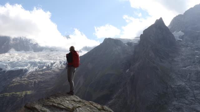 Female hiker climbs rock ridge above valley, mountains