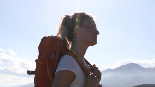female hiker climbs to summit above sea and valley - rucksack stock videos & royalty-free footage