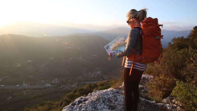 Female hiker consults map on rock ledge, hills distant, sunrise