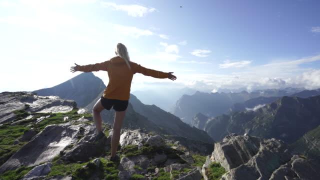 vídeos de stock, filmes e b-roll de caminhante fêmea que faz a ioga na parte superior da montanha, alargamento do sol e céu azul, e montanhas abaixo - pose de arvore
