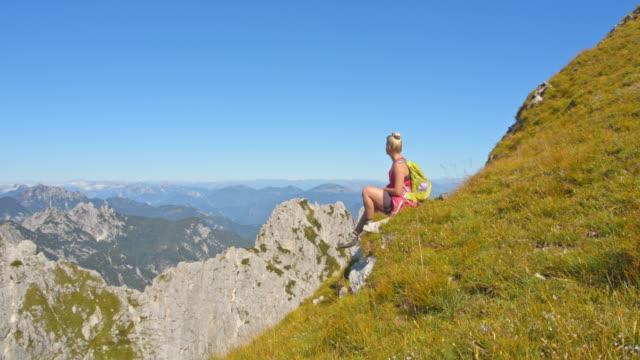 stockvideo's en b-roll-footage met ws vrouwelijke wandelaar genieten van een berglandschap uitzicht - julian alps