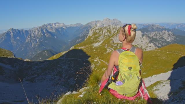 stockvideo's en b-roll-footage met ws vrouwelijke wandelaar genieten van majestueuze berglandschap uitzicht - julian alps