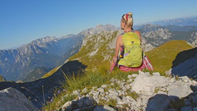 stockvideo's en b-roll-footage met ws vrouwelijke wandelaar genieten van het uitzicht op de julische alpen - julian alps