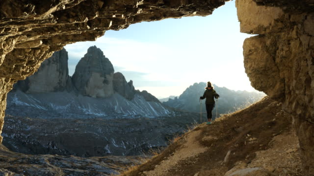 female hiker exits mountain cave towards sunset, view of mountains below - kosmetisches stirnband stock-videos und b-roll-filmmaterial