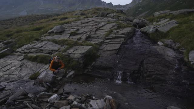 weibliche wanderer füllt sich . wasserflasche in süßwasserstrom in den bergen - bach stock-videos und b-roll-filmmaterial