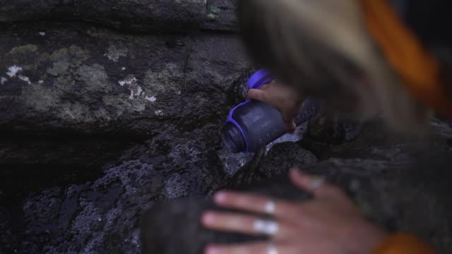 vídeos de stock e filmes b-roll de female hiker fills up water bottle in fresh water stream in mountains - encher atividade