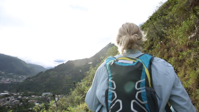 vídeos de stock e filmes b-roll de pov of female hiker following mountain trail, above village - mala de ombro