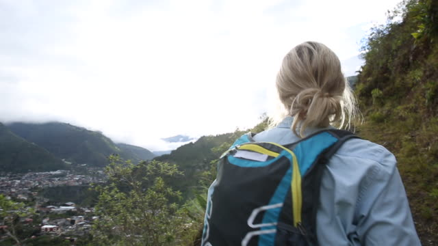 pov of female hiker following mountain trail, above village - kletterausrüstung stock-videos und b-roll-filmmaterial