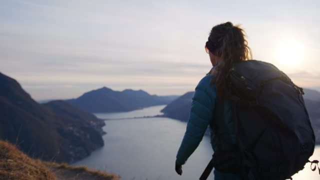female hiker follows mountain trail to viewpoint over lake and sunset - active lifestyle stock videos & royalty-free footage