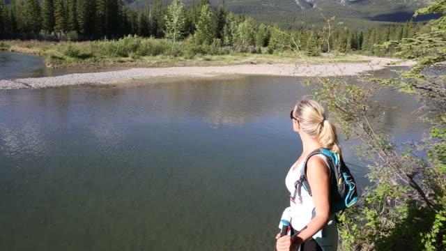 vídeos de stock e filmes b-roll de female hiker follows path along mountain river, through forest - olhar em redor