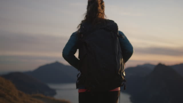 female hiker follows trail to mountain top with view of city, lake and sunset below - hiking stock videos & royalty-free footage