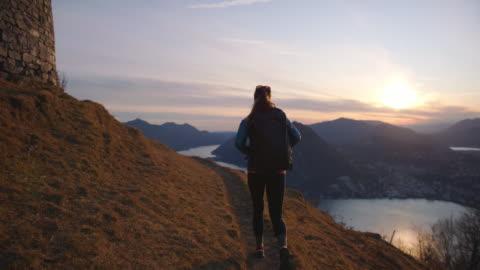 女性ハイカーは、下の都市、湖と夕日の景色を望む山頂へのトレイルをたどります - active lifestyle点の映像素材/bロール