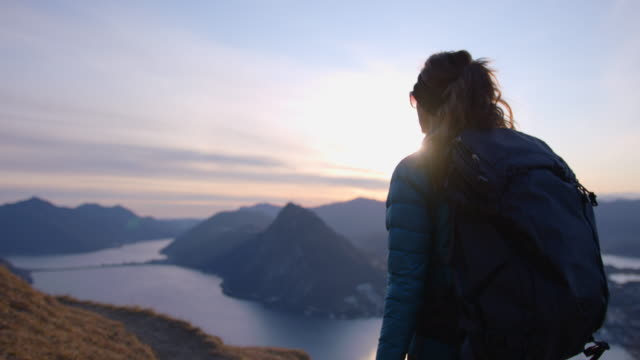 female hiker follows trail to viewpoint of lake and mountains at sunset - esplorazione video stock e b–roll