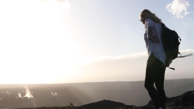 female hiker hoists backpack, walks along ridge crest - hochziehen stock-videos und b-roll-filmmaterial