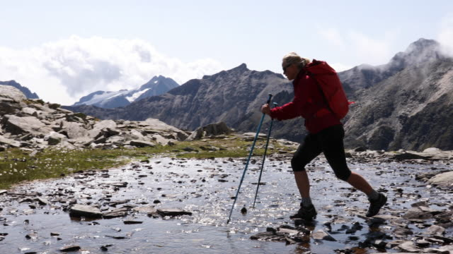 vídeos de stock, filmes e b-roll de female hiker hops between stepping stones in creek, mountains - riacho