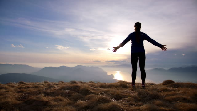 female hiker in freedom pose looks out at view, lake and mountains below - ausgestreckte arme stock-videos und b-roll-filmmaterial