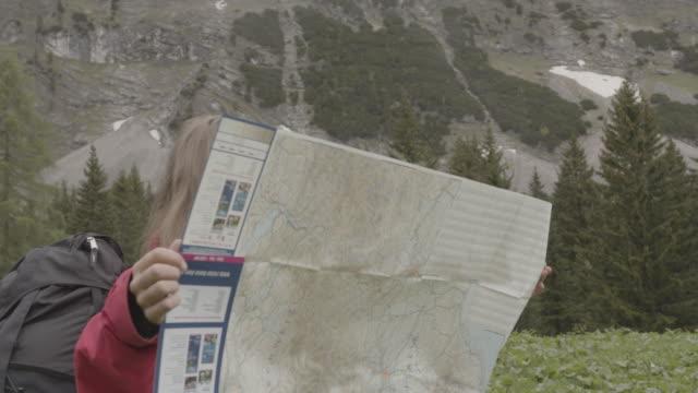 kvinnlig vandrare i röd kassan ut en karta framför träd och berg - endast unga kvinnor bildbanksvideor och videomaterial från bakom kulisserna