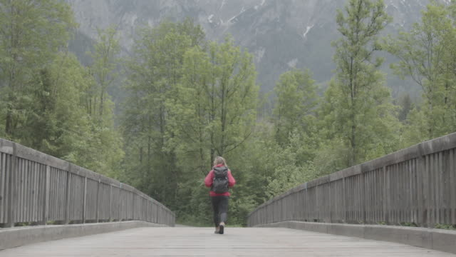 female hiker in red walking across a wooden bridge away from camera - boundary stock videos & royalty-free footage